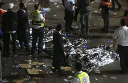 Ultra-Orthodox Jewish men stand next to covered bodies after dozens of people were killed and others injured after a grandstand collapsed in Meron, Israel, where tens of thousands of people were gathered to celebrate the festival of Lag Ba'omer at the site in northern Israel early on April 30, 2021. - Dozens of people were killed in a stampede at a Jewish pilgrimage site in the north of Israel on early on April 30, rescue services said.  Tens of thousands of Jews were participating in the annual pilgrimage on Thursday, for the feast of Lag BaOmer. But after midnight, a grandstand collapsed, triggering scenes of panic. (Photo by David COHEN / JINI PIX / AFP) / Israel OUT